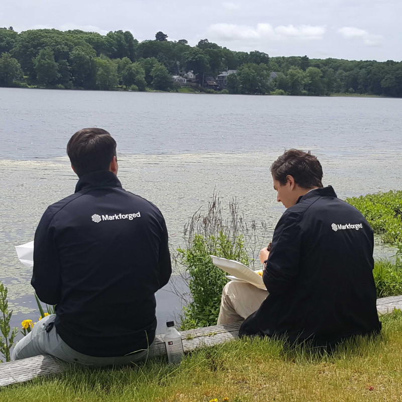 Picture of two team members in front of a lake with their Markforged jackets on