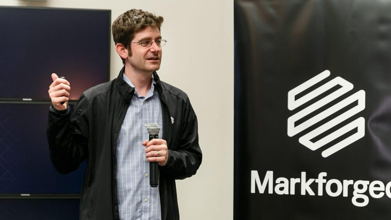 Great speaking at an event in front of a Markforged sign
