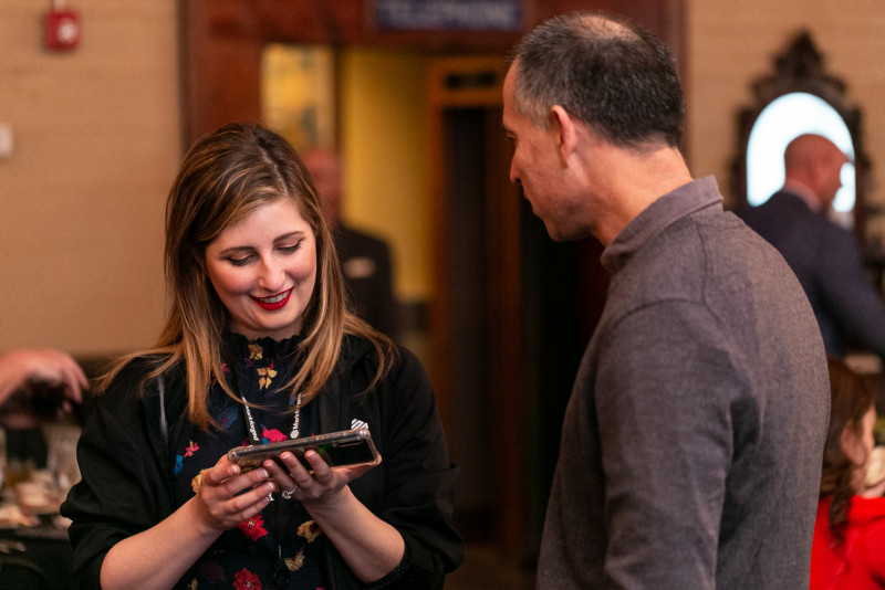 Photo of a Markforged employee showing her phone to a partner at an event